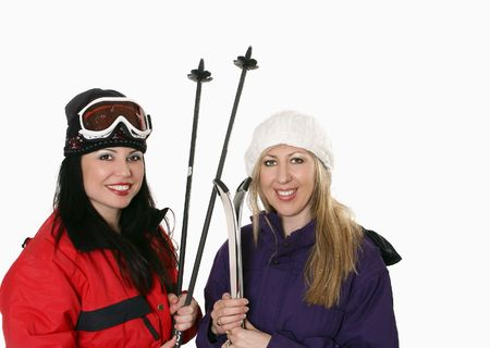 Two women dressed in warm parkas and holding skis photo