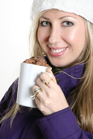 decadent: Woman dressed in warm winter clothing relaxes with a mug of decadent chocolate drink. Stock Photo