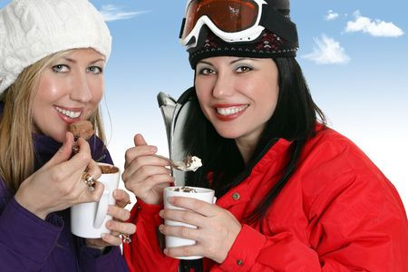 decadence: Winter indulgence - two women enjoy hot drinks topped with delicious creamy toppings.