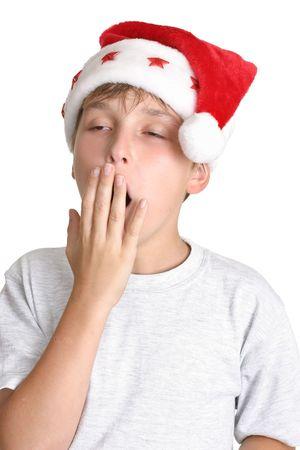 cansancio: �Cansado de compras de Navidad? Un ni�o que demuestra tiredness o el aburrimiento. �l est� usando una camisa y un sombrero grises de santa.