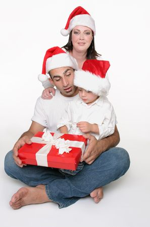 Mum and dad give their young  toddler a Christmas present. Stock Photo - 663726