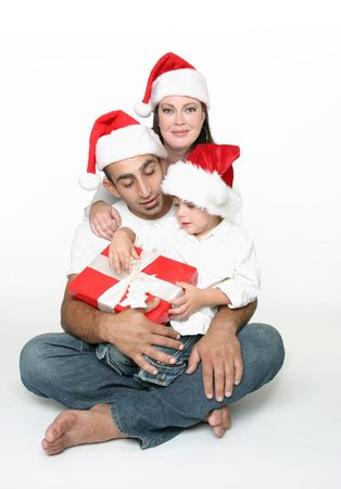 Parents watch as a young toddler begins to unwrap a present. Stock Photo - 663724