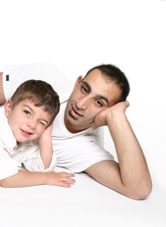 pre adult: Dad on floor with cheeky son winking one eye, space for text.