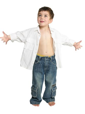 extrovert: Extroverted toddler boy wearing blue jeans and white shirt stands with arms outstretched. Stock Photo