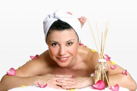 indulgere: Day Spa di lusso. Sorridente donna indossa testa turbante rilassa tra petali di rosa e fragrante aroma di bastoni.