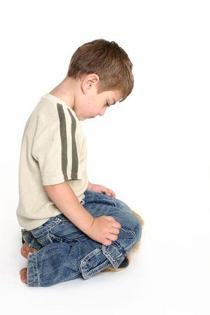 bad behavior: A toddler bows his head in shame.