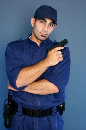 guardia de seguridad: Oficial de seguridad en arma que sostiene uniforme. Foto de archivo