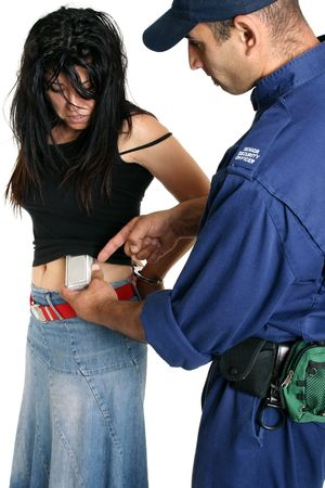 wrongdoing: Shoplifting.  A security guard removes a concealed shoplifted item from a criminal Stock Photo
