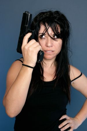 Gangster Girl.  Grungy looking girl holding a gun in her hand Stock Photo - 714501