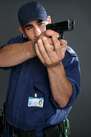 security uniform: Security officer takes aim with his gun.  Please note:  Badge photo is same person and was photographed by me.  No extra release required.