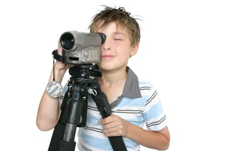 tripod: Child creating a short movie using video camera and tripod.  Whtie background
