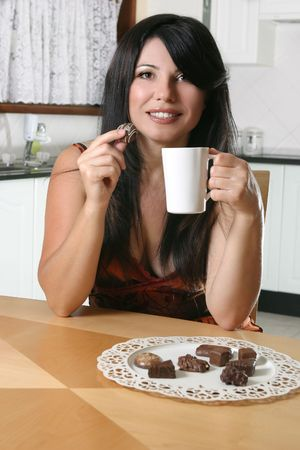 A beautiful woman enjoys coffee and chocolates. Stock Photo - 753715