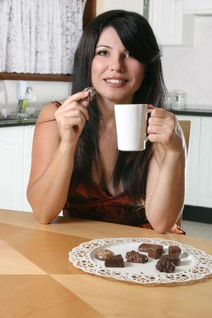 A beautiful woman enjoys coffee and chocolates. Stock Photo - 753715