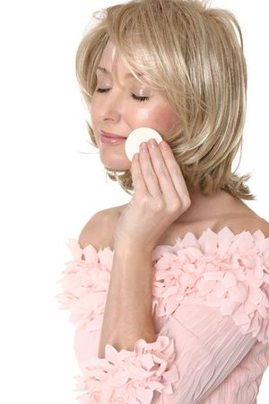 A woman removing, applying or touching up makeup to her face photo