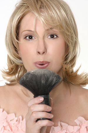 loose skin: A female blowing gently to remove excess loose powder from a brush. Stock Photo