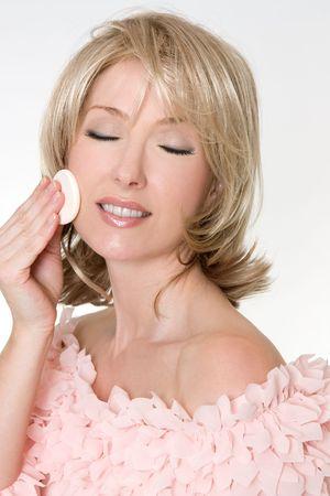 empezar: Una mujer del adulto usando una esponja cosm�tica para comenzar a quitar maquillaje.