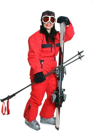 Female skier wearing a red ski suit and carryng matching skis and poles. photo