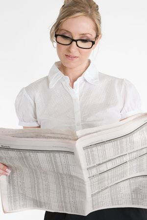 financial newspaper: A businesswoman reading the financial newspaper.  Please note newsprint has been artificially blurred to render company names illegible.
