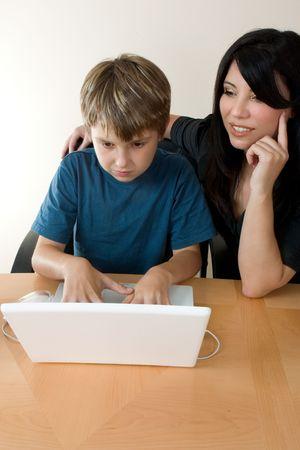 supervisi�n: Ni�o utilizando un ordenador con la supervisi�n de un adulto.  Foto de archivo