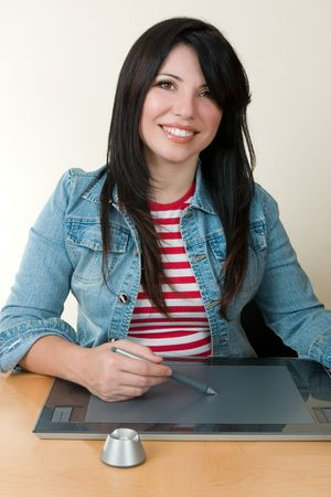 Graphic artist or retoucher.  A smiling woman sitting at desk using a graphic tablet photo
