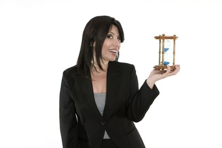 sand timer: Time on your hands.   A businesswoman holding a traditional sand timer in her hand. You could change the sandtimer for another product.