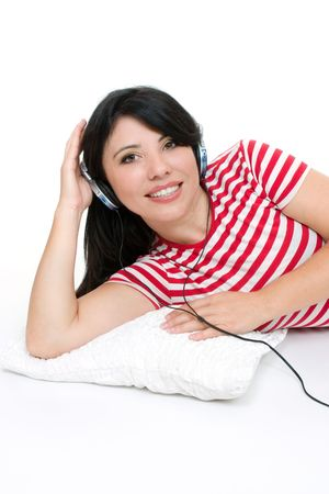 aural: Female lying down and listening to music through headphones.