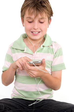 Child sitting down using a digital player.  He is wearing a striped polo shirt and jeans. photo