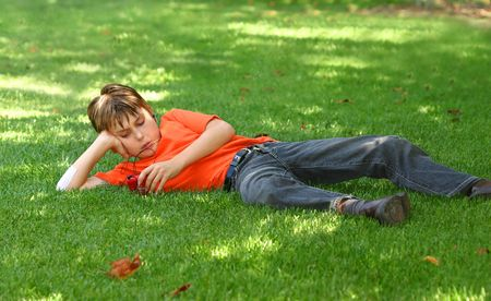 sprawled: a young boy sprawled out on the shaded grass in the park, listens to music on an mp3 music player.