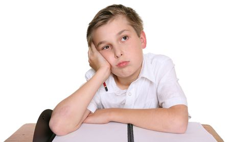 A school student with head resting on one hand, siting in front of an empty book,  lost in thought, daydreaming, or thinking about what to write Stock Photo