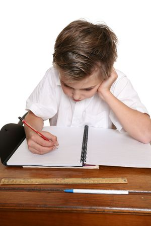 scholastic: A school pupil sitting at desk doing classwork or homework.