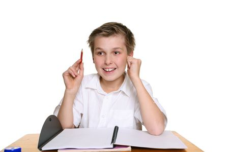 comprehension: Happy school student sitting at desk with an idea or answer Stock Photo