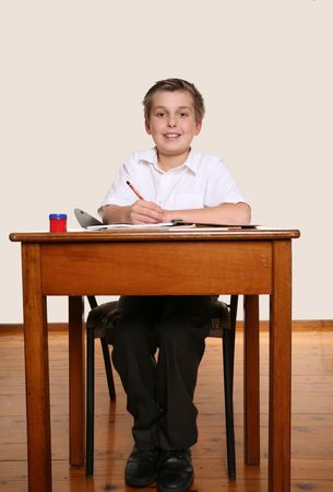scholastic: Happy smiling young school boy sitting at school desk Stock Photo