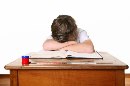 frustrated student: A unhappy or frustrated schoolboy sitting at desk and bent over with head in hands