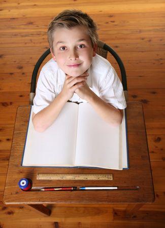 garçon ecole: Confiant �cole gar�on assis en classe avec livre ouvert.