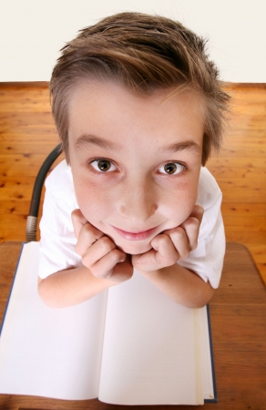 scholastic: Comical geeky schoolboy with a book looking up.  Focus to face only.