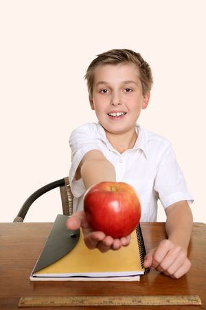 A child holds out an apple for his teacher.