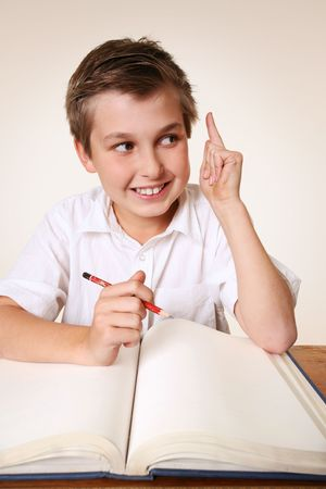 scholastic: Brainchild idea.  Student school boy sitting at desk with school books has an inspirational idea Stock Photo