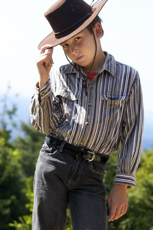 courteous: A courteous country boy in denim jeans and button shirt tips his hat. Stock Photo