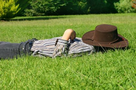 countrylife: A child lays in grassy field taking a rest or siesta.