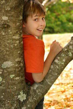 A child leaning against the trunk of a deciduous tree in the Autumn Stock Photo - 1134148