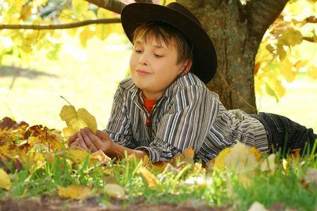 chłopięctwo: Dziecko odpoczynku na przestrzeniach drzewa i spadł z gry jesienią liści. Proces ten zmienia kolor liści jest photoperiodism, zdolność roślin do pomiaru długości światła i dostosować odpowiednio - proszę pamiętać 400iso F7 Zdjęcie Seryjne
