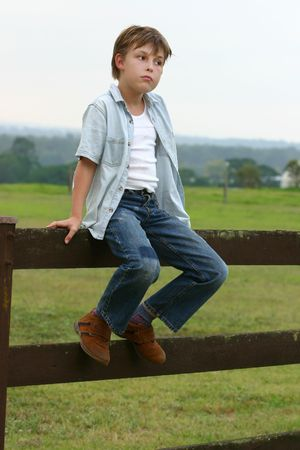 pasture fence: Farm boy sitting on a wooden fence in late afternoon dusk. Stock Photo