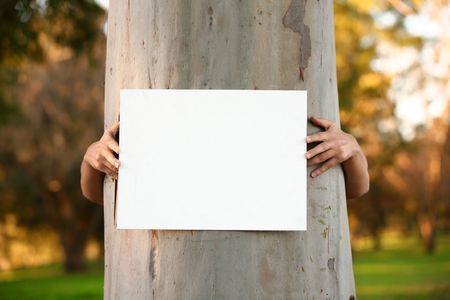 Environmentalist protester arms hugging large tree trunk and holding a blank sign ready for any message or statement