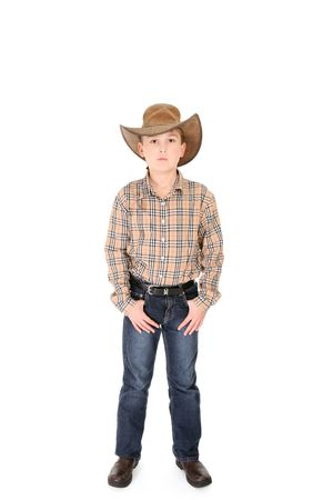 A young cowboy standing with feet apart on a white background. photo