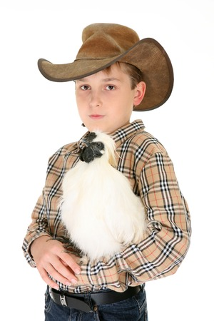 A rural boy carrying a silkie chicken in his arms.  Silkie Bantams are excellent birds to keep as a pet. They are quite gentle and adapt well to human handling. The Silkie bantam is docile by nature and craves attention. photo