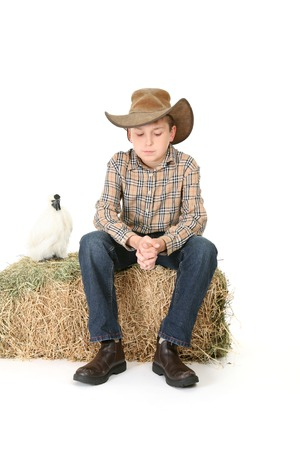 akubra: A country boy sitting on a bale of lucerne hay thinks quietly.