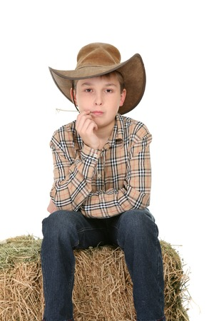 akubra: A child sits on  a bale of lucerne and casually chews on a piece. Stock Photo