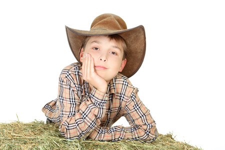 A country farm boy leaning on a bale of lucerne hay. photo
