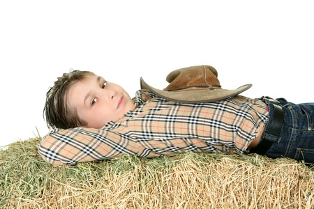 Country boy in checked shirt and jeans rests on a bale of lucern hay.