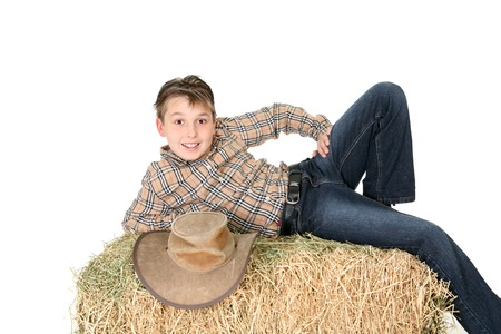 A boy from the country lays casually on a hay bale and smiles.  White background. photo